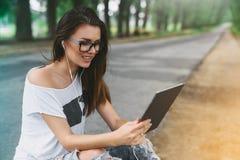 Muchacha hermosa y feliz, con los vidrios para la vista, usando la tableta y los auriculares en el parque al aire libre Imagen de archivo