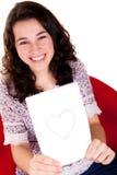 Muchacha hermosa y feliz que le muestra el corazón Foto de archivo libre de regalías