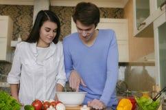 Muchacha hermosa y muchacho que preparan el desayuno en la cocina imagen de archivo libre de regalías