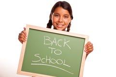 Muchacha hispánica bonita que sostiene la pizarra con de nuevo a la escuela Fotos de archivo