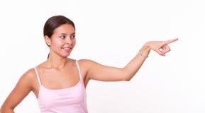 Muchacha hispánica elegante que señala a su izquierda Fotos de archivo libres de regalías