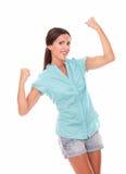 Muchacha hispánica feliz en camisa azul con el brazo para arriba Fotografía de archivo