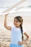 Muchacha hispánica linda que juega con el plano del juguete en la playa imagen de archivo