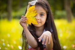 Muchacha hispánica linda que oculta sobre la hoja amarilla Foto de archivo