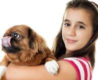 Muchacha hispánica que lleva un pequeño perro Foto de archivo
