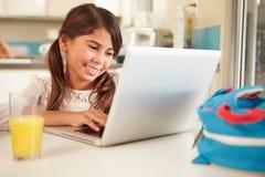 Muchacha hispánica que se sienta en la tabla usando el ordenador portátil Fotografía de archivo libre de regalías