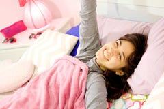 Muchacha hispánica sonriente linda en despertar de bostezo de la cama en el primer de la mañana Fotografía de archivo libre de regalías