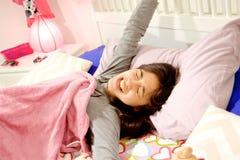 Muchacha hispánica sonriente linda en despertar de bostezo de la cama por la mañana Foto de archivo