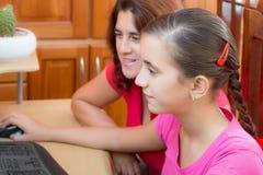Muchacha hispánica y su madre joven que trabajan en un ordenador Imagen de archivo libre de regalías