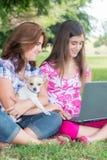 Muchacha hispánica y su madre que hojean el web al aire libre Fotografía de archivo libre de regalías