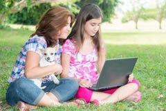 Muchacha hispánica y su madre que hojean el web al aire libre Fotos de archivo