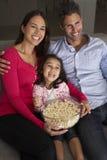 Muchacha hispánica que se sienta en Sofa And Watching TV con los padres Imagen de archivo libre de regalías