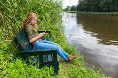 Muchacha holandesa que lee el teléfono móvil en banco en naturaleza Imagenes de archivo