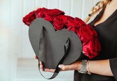 Muchacha hollding arreglos hermosos de las rosas Imagenes de archivo