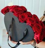 Muchacha hollding arreglos hermosos de las rosas Fotografía de archivo