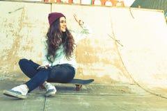Muchacha impresionante del skater con la sentada al aire libre del monopatín en el skatepark Imágenes de archivo libres de regalías
