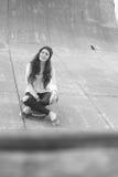 Muchacha impresionante del skater con la sentada al aire libre del monopatín en el skatepark Fotos de archivo libres de regalías