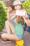 Muchacha impresionante del skater que hace el selfie en el teléfono móvil Imagen de archivo