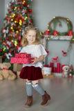 Muchacha impresionante linda que celebra la Navidad del Año Nuevo cerca del árbol de Navidad por completo de juguetes en vestidos Fotografía de archivo