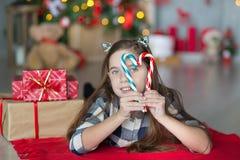 Muchacha impresionante linda que celebra la Navidad del Año Nuevo cerca del árbol de Navidad por completo de juguetes en vestidos Imágenes de archivo libres de regalías