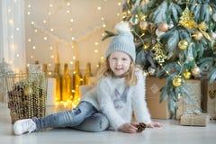Muchacha impresionante linda que celebra la Navidad del Año Nuevo cerca del árbol de Navidad por completo de juguetes en vestidos Imagen de archivo libre de regalías