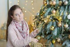 Muchacha impresionante linda que celebra la Navidad del Año Nuevo cerca del árbol de Navidad por completo de juguetes en vestidos Fotos de archivo