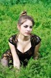 Muchacha impresionante que se sienta en la alta hierba Fotos de archivo libres de regalías