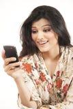 Muchacha india atractiva que usa su teléfono celular. Imagenes de archivo