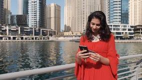 Muchacha india con el teléfono y tarjeta de crédito en un embarcadero en el puerto deportivo de Dubai almacen de metraje de vídeo