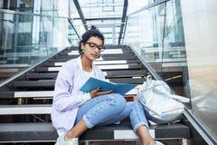 Muchacha india linda joven en el edificio de la universidad que se sienta en las escaleras que lee un libro, vidrios del inconfor Fotografía de archivo