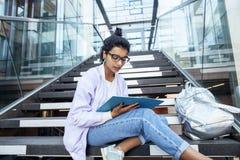 Muchacha india linda joven en el edificio de la universidad que se sienta en las escaleras que lee un libro, vidrios del inconfor Imagen de archivo libre de regalías