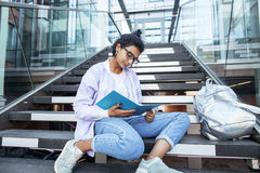 Muchacha india linda joven en el edificio de la universidad que se sienta en las escaleras que lee un libro, vidrios del inconfor Foto de archivo libre de regalías