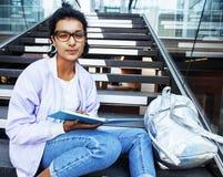 Muchacha india linda joven en el edificio de la universidad que se sienta en las escaleras que lee un libro, vidrios del inconfor Imagenes de archivo