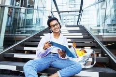 Muchacha india moderna linda joven en el edificio de la universidad que se sienta en las escaleras que lee un libro, vidrios del  Fotografía de archivo libre de regalías