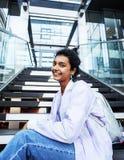 Muchacha india moderna linda joven en el edificio de la universidad que se sienta en las escaleras que lee un libro, vidrios del  Imagen de archivo