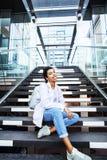 Muchacha india moderna linda joven en el edificio de la universidad que se sienta en las escaleras que lee un libro, vidrios del  Foto de archivo