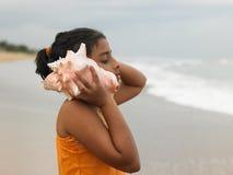 Muchacha india que escucha una concha Foto de archivo