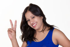 Muchacha india que lleva una camiseta sin mangas azul que muestra sig de la victoria Foto de archivo