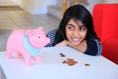 Muchacha india que mira a su Piggybank Imagenes de archivo