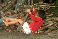 Muchacha indonesia en un oscilación Foto de archivo libre de regalías