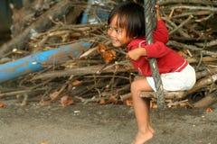 Muchacha indonesia en un oscilación Imagenes de archivo