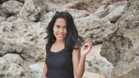 Muchacha indonesia que presenta en una playa hermosa y rocosa en Bali Idonezia almacen de video