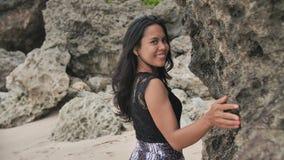Muchacha indonesia que presenta en una playa hermosa y rocosa en Bali Idonezia metrajes