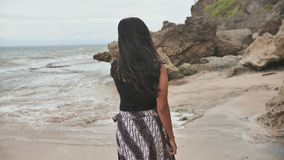 Muchacha indonesia que presenta en una playa hermosa y rocosa en Bali Idonezia almacen de metraje de vídeo