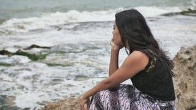 Muchacha indonesia triste en la orilla rocosa de la isla de Bali metrajes