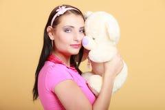 Muchacha infantil de la mujer infantil que abraza el oso de peluche Foto de archivo libre de regalías