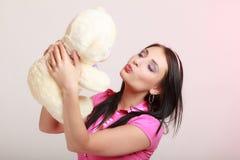 Muchacha infantil de la mujer infantil que besa el oso de peluche Foto de archivo libre de regalías