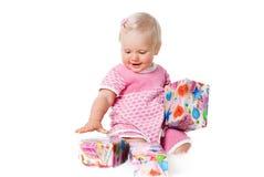 Muchacha infantil feliz con los rectángulos de regalo en blanco Foto de archivo libre de regalías