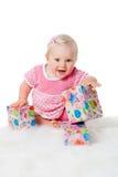 Muchacha infantil feliz con los rectángulos de regalo en blanco Imagen de archivo