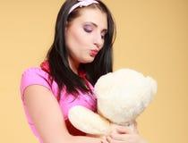 Muchacha infantil infantil de la mujer joven en juguete rosado del oso de peluche que se besa Imagen de archivo libre de regalías